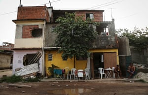 People sit in the mostly demolished Vila Autodromo favela community