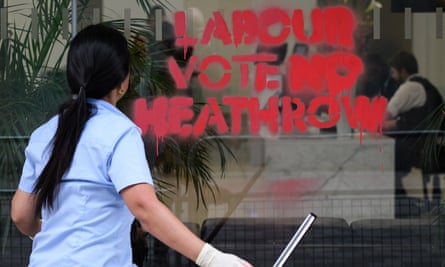 A woman cleans graffiti from the windows of the Labour Party headquarters following a protest by campaigners, calling for Labour to stop the planned expansion of Heathrow, 4 June in London