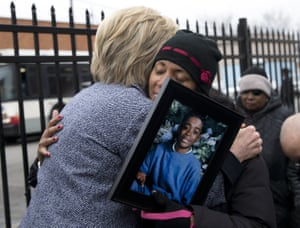 Hillary Clinton hugs a mother holding a portrait of her son who was killed by gun violence at the Kids off the Block memorial to children killed by gun violence in Chicago.