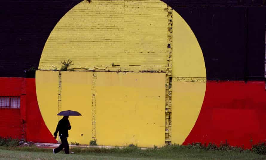 A person walks past an Aboriginal flag painted on a wall