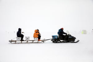 Scientists riding on a sled towed by a snowmobile