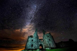 Alnwick, UK. A starry sky over the ruins of the great gatehouse at Dunstanburgh Castle