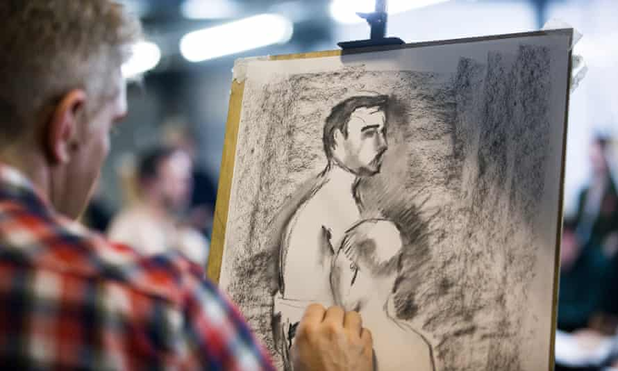 A man sketches two nude men during a life drawing class