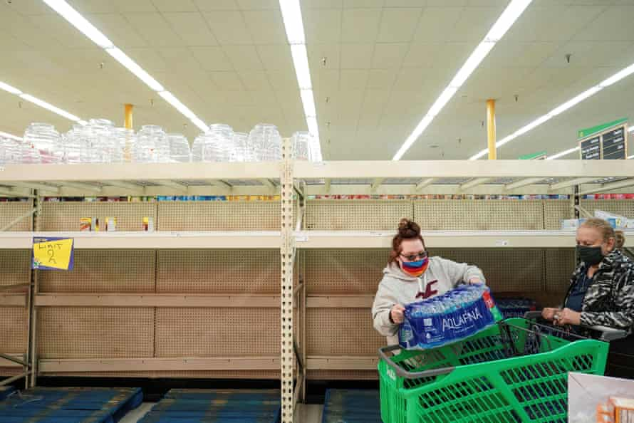 Shoppers at a Houston supermarket pass bare shelves. The winter weather has caused water and food shortages.