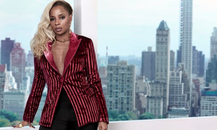 Mary J Blige, in a pink and black stripped jacket with a shiny pink lapel, standing in front of a window, the New York skyline behind her.