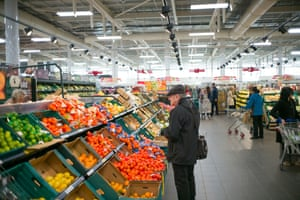 Shopper looking at fruit and vegetables in shop