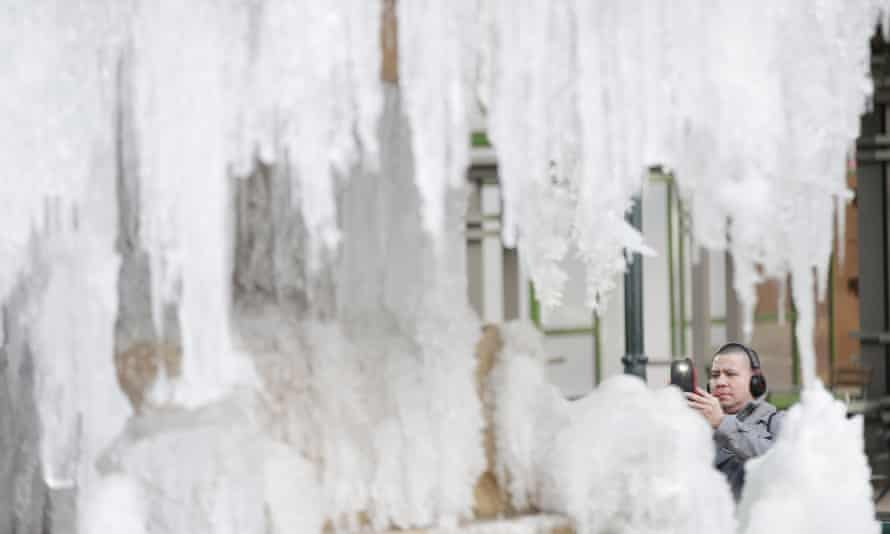 A man takes a photo of the frozen fountain in Bryant Park in New York City on January 3, 2018. A huge winter storm called a 'bomb cyclone' is set to batter the north-east this week leaving the city blanketed in snow and battling harsh winds.