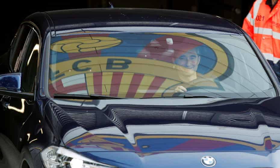 Barcelona's coach Ernesto Valverde leaves Joan Gamper training camp, as the team's logo is reflected on the window of his car.