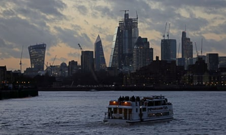 A boat cruises down the Thames as the sun sets behind Canary Wharf