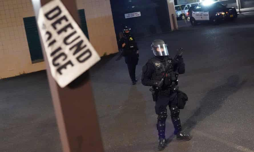 A Portland police officer guards the Portland police bureau north precinct earlier this month.