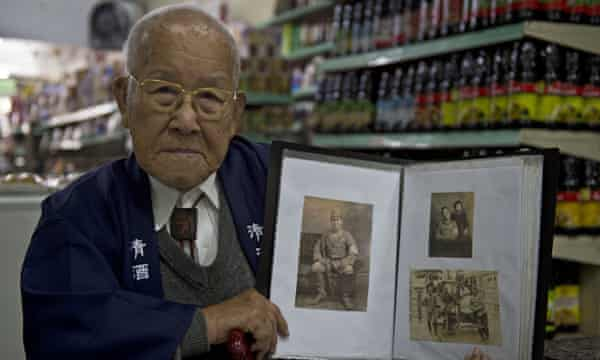 Takashi Morita shows a picture album of his youth in Hiroshima at his grocery store in São Paulo.
