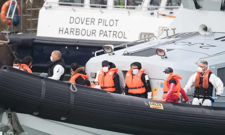 Migrants arrive in Dover on a Border Force vessel after being intercepted while crossing the Channel.