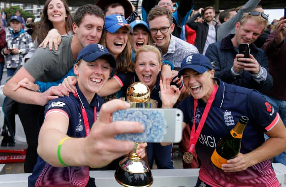 The England women's cricket team captain Heather Knight, left, and team-mate Katherine Brunt celebrate with the trophy and fans after victory in the World Cup Final against India at Lords Cricket Ground.