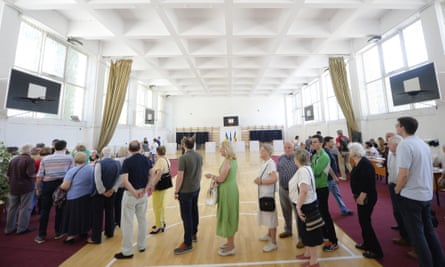 People wait in line to cast their vote as a higher than usual voter turnout is registered in Bucharest, Romania.