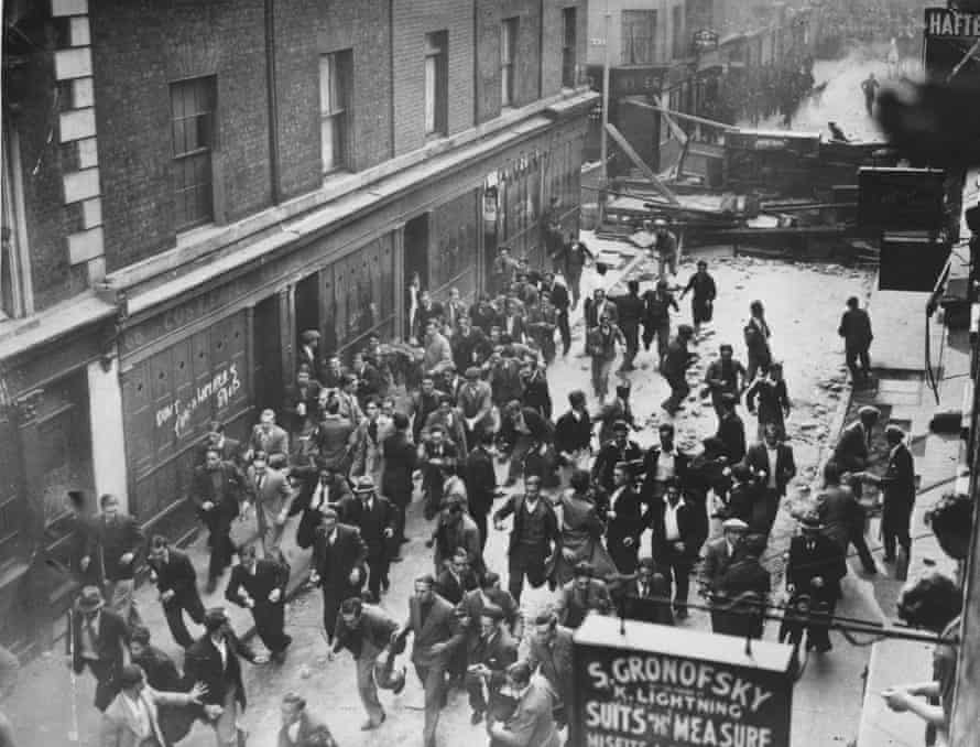 Demonstrators flee as police break down a barricade in Cable Street during the battle.