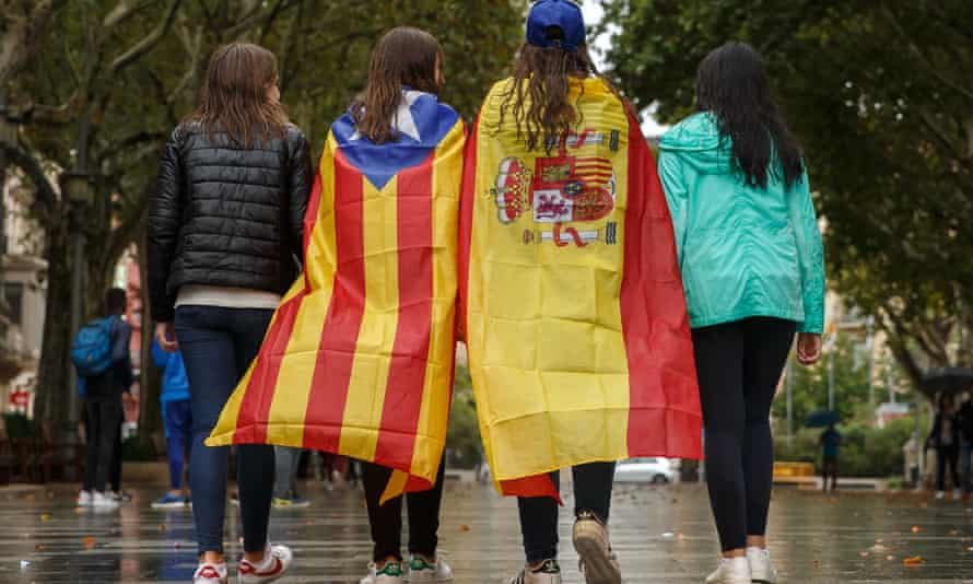 Girls stroll through the center of Figueras with the Spanish and a pro-independence Catalan flag