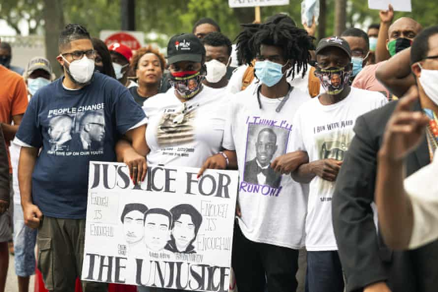 On 16 May, Ahmaud Arbery's aunt Theawanza Brooks, center left, joins other family members and supporters in a march from the Glynn county courthouse to a police station.