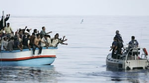 Armed Forces of Malta marines toss bottles of water to a group of around 180 illegal immigrants as a rescue operation gets underway.