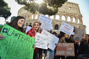 """In front of the Coliseum in Rome, students hold placards reading: """"Earth is warming"""", """"we can't drink, we can't breathe"""", """"let's raise our voices, not the sea level"""" and """"we will study the past if you give us a future"""""""
