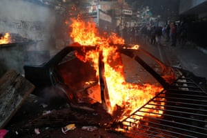Demonstrators stand close to the remains of a burning car used as barricade. Guaido declared himself interim president of Venezuela - a move that was quickly recognised by US President Trump - in fight against President Maduro whose presidency Guaido considers 'illegitimate'