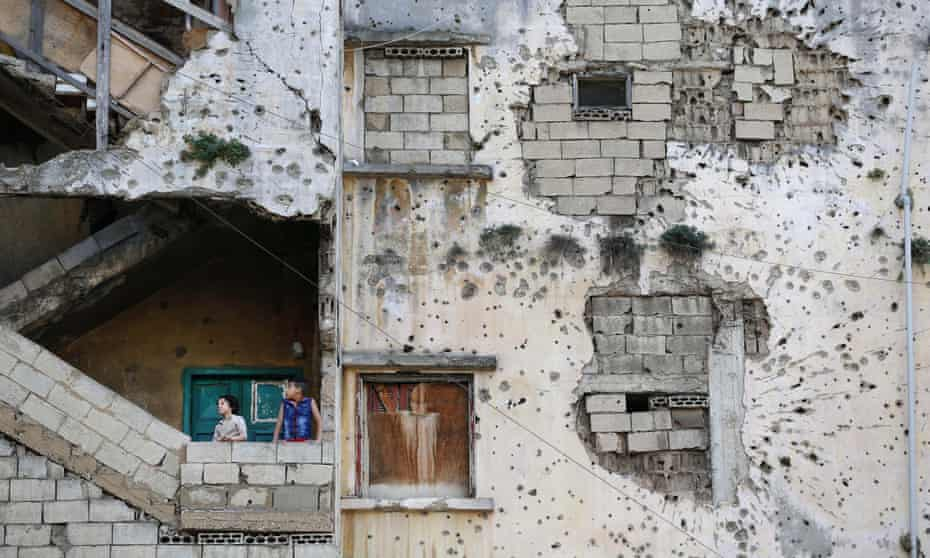 Syrian refugee children stand on the stairs of their Beirut apartment building, damaged long ago during Lebanon's own civil war.