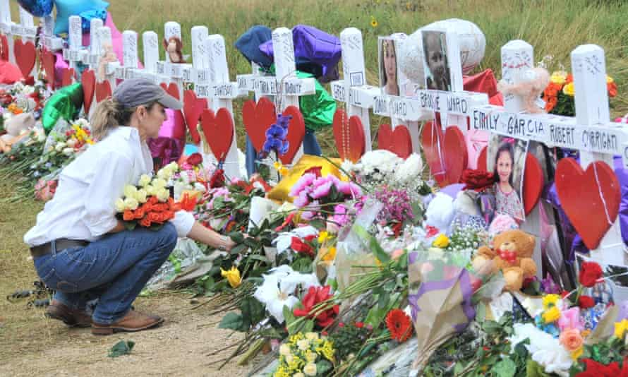 A woman lays flowers at a memorial site for victims of the shooting in Sutherland Springs, Texas