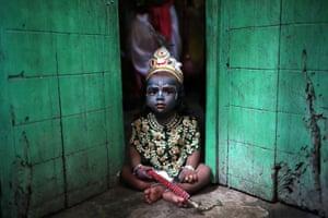 Dhaka, Bangladesh: a child dressed as Lord Krishna sits on a doorstep during the Janmashtami festival