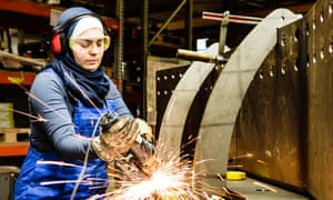 Young female trainee works with a grinder in a workshop, flying sparks