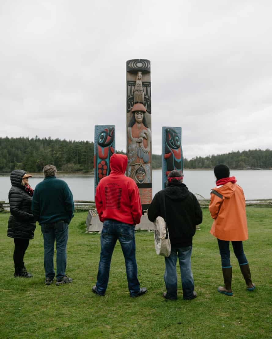 Lummi tribal members wait for hereditary chief Bill James to speak at English Camp on the Puget Sound following a ceremonial feeding of the qwe 'lhol mechen, commonly known as orcas, Wednesday, April 10, 2019 in Washington.