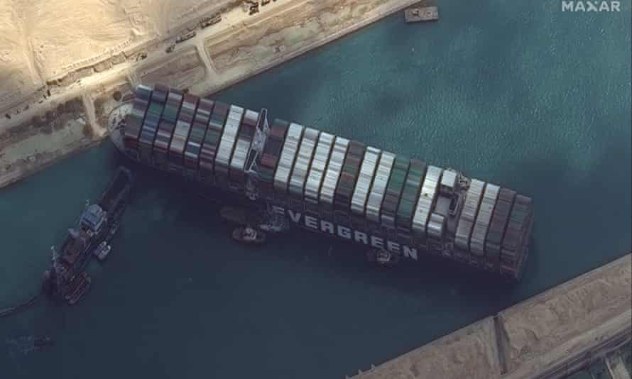 A view from above of the Ever Given ship stuck sideways in the Suez Canal.