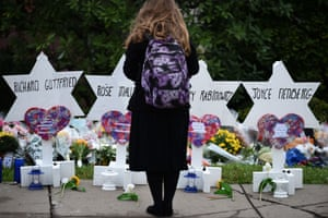 A woman stands at a memorial outside the Tree of Life synagogue after a shooting there left 11 people dead in the Squirrel Hill neighbourhood in Pittsburgh on 27 October