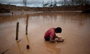 A boy searches for gold at an illegal mine in La Pampa, in the Madre de Dios region of Peru, 2014.