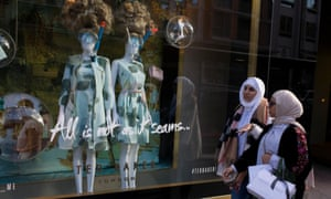 Two women walk past a display of mannequins in diving masks and snorkels, outside a central London branch of Ted Baker.