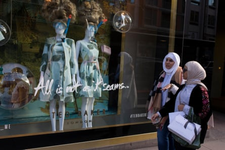 Two Muslim women walk past a shop display in central London.