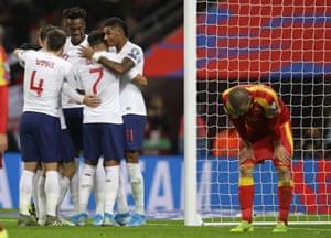 England's players celebrate Montenegro's Aleksandar Sofranac (on the right) scoring an own goal.