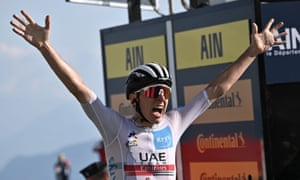 Tadej Pogacar celebrates as he crosses the finish line at the Grand Colombier.