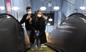 A couple wearing face masks travel on the Underground in London on 24 March.