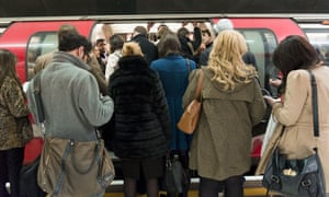 People try to get on a Central line train in London