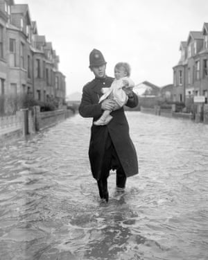 One year old Christine Philpot being rescued by a policeman after flooding in Lowestoft, Suffolk, on 1 February 1953