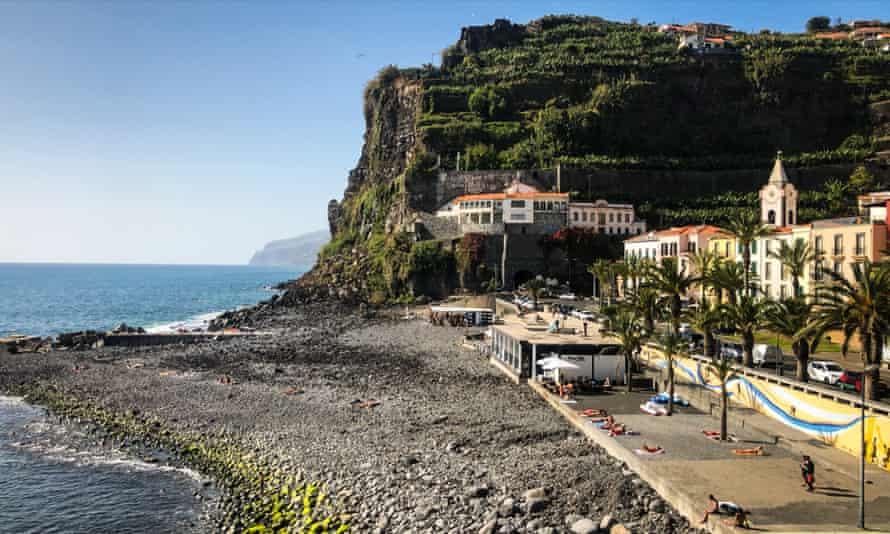 A lush green hill overlooks a rocky beach on Madeira