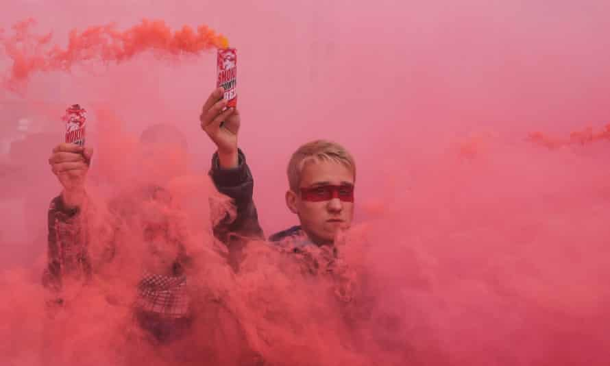 A young man holds a red smoke bomb to send a signal to attendees during a rally at Independence Square in Kyiv, Ukraine.