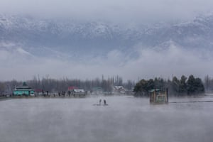 Kashmiri men row their makeshift raft made of plastic pipes on the Dal Lake after a brief spell of fresh snowfall on the outskirts of Srinagar.