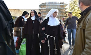 Nuns leave the centre of Norcia on Sunday after the earthquake hit