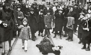 A crowd surround a dead man on the street in the Warsaw ghetto around 1940.