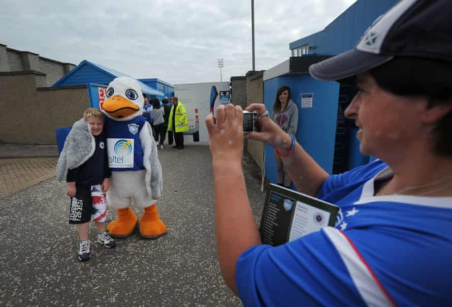A young Rangers fan poses for a photograph with the Peterhead mascot Sammy the Scurry before the Scottish Third Division match at Balmoor Stadium in August 2012
