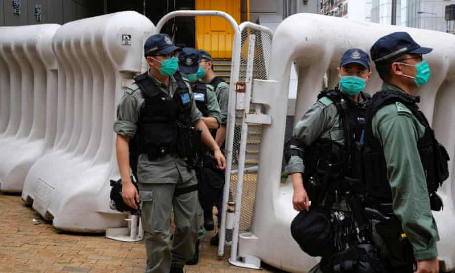 Riot police patrol near China's liaison office in Hong Kong