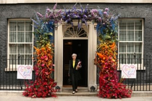 London, UK. Prime minister, Theresa May, leaves No 10 Downing Street, which is adorned with a multi-coloured floral display in honour of a Pride reception that took place the day before