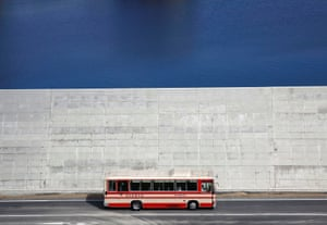 A bus drives past a sea wall in Yamada
