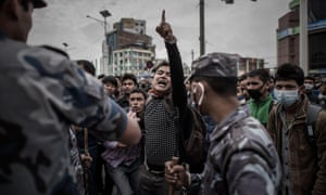 Nepalese riot police officials stand alert on a street in Kathmandu as earthquake survivors desperate to leave the Nepalese capital show their anger after promised special bus services failed to materialise.