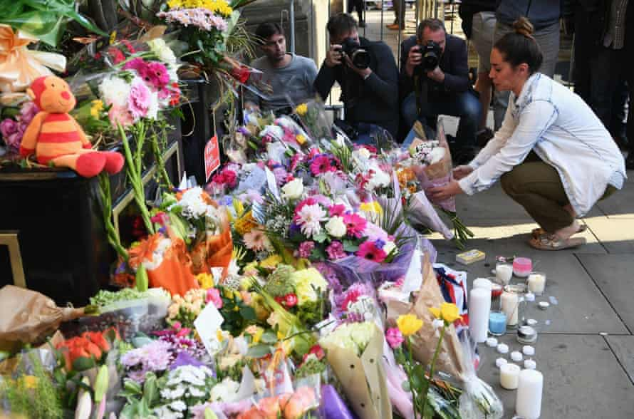 A woman lays flowers at the vigil.